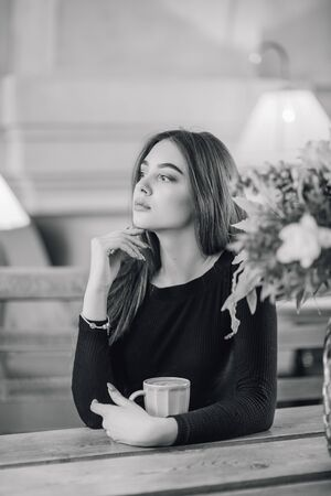 Portrait of a girl. Brunette in a coffee shop. elegant lady in a black dress, in a restaurant alone. Girl in a cafe. Black and white photography. Pensive mood of a beautiful girl