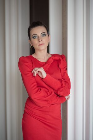 Young girl in a red dress. Brunette in a red light dress indoors. Pensive model. Emotions of a modern lady. Young woman portrait. Portrait. Gorgeous woman 20 or 21 years old.