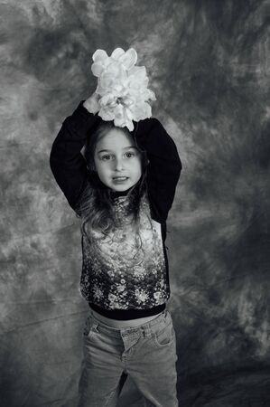 Cute little girl. Little girl and flower in the studio. Child with flowers in hands