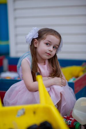 Cute five year old girl in a pink princess dress. portrait of a happy cute blonde girl 5 years old. Little girl with two ponytails and white bows. Child