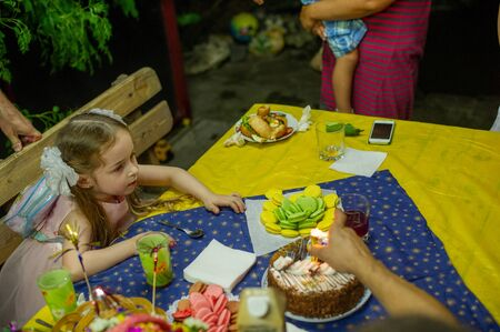 Laughing kid girl 5-6 year old eating birthday. Childhood. Girl 5 years old birthday.