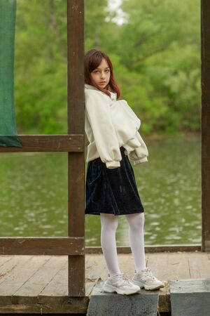 A schoolgirl stands by the river in a blue dress. Spring, childhood, nature. Portrait of a little girl nine years old. A little girl in a white coat stands by the birch. Portrait of a teenage girl Stock fotó