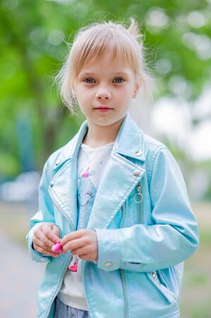 Close up portrait of young 6-7 year old girl. Girl 7 years old outdoors portrait in a blue jacket. Little girl with blue hair in a blue jacket on the street in spring. Childhood walk.