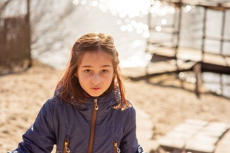 girl on the background of winter lake or river. winter season. Girl in winter clothes on a background of the river. Girl 9 years old against the background of a small river. Teen girl in a blue jacket