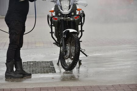 Motorcycle Car Wash Motorcycle Big Bike cleaning with foam injection Make more clean. A series of photos a biker washes his motorcycle at the car wash. Black-white-red color of the bike. Clean vehicle