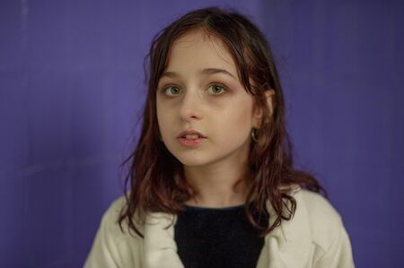 Portrait of a girl looking to the photographer after rain. Girl with wet hair after the rain. A teenager in a white coat with drops of water from the rain on his face. A girl on a purple background. Stock fotó