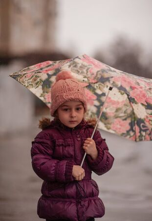 Little girl under the umbrella outside, rainy day. Little girl walks with umbrella under the rain. A child in a pink hat and a purple jacket on a rainy day