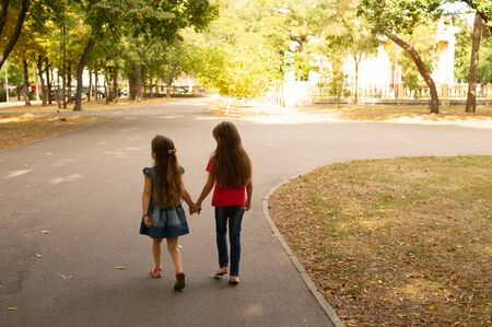 Sisters, Outdoor photo from two little girls. Two little girls walk in the park by the hand. Sisters for a walk in the summer or autumn on the street. Girlfriends, children, nature. Family concept. Stock fotó