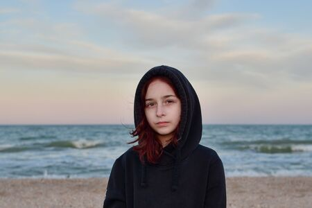 Portrait Of A Model In A Fashionable Jacket At Sunset By the sea. Teenager in a black hoodie and the sea. Man and the sea. Pensive girl in a hood by the sea in the summer at sunset. Girl 9 years old. Banque d'images