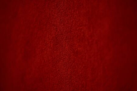 Blood red bath towel background. The texture of the fabric is red terry. Texture fabric for designers, towel