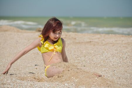 Girl 9 years old at sea. The portrait of the young girl about 9-12 years old. Teenager summer vacation sand. Sunny day and the sea. Childhood travel vacation. Little girl rejoices in pestilence.