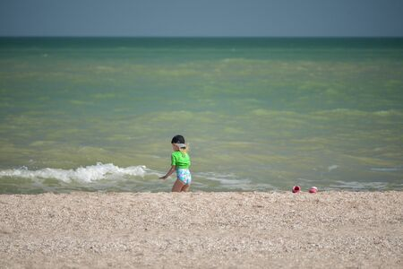 Little girl 5 years old near the sea. Girl 5 years old near the sea in a green T-shirt and a cap. Sea vacation concept Фото со стока