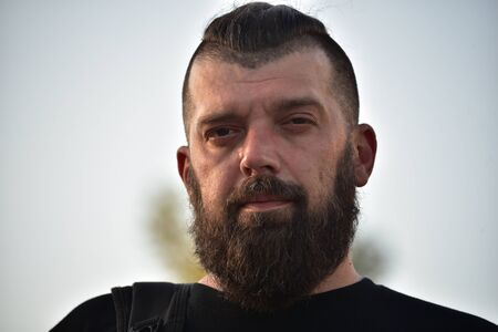 Man with a beard at sunset. Large facial portrait of a bearded man of 40 years. Portrait full face. Man in a black T-shirt
