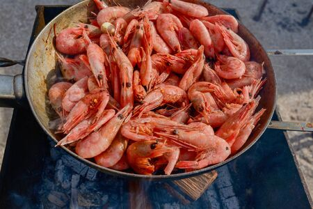 shrimp. Shrimps are cooked in a pan over a fire. Bonfire seafood