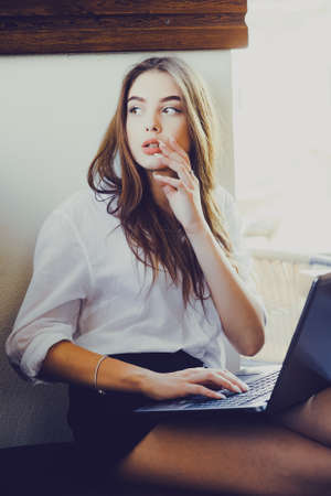 Young beautiful business woman working on a laptop. Beautiful girl in a white shirt at the computer. business woman economist in formal wear concentrated, in front of laptop, stylish, ponder, serious