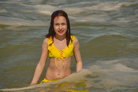 Girl at sea. The portrait of the young girl. Teenager summer vacation sand. Sunny day and the sea. Childhood travel vacation. Teenager in a yellow swimsuit on the beach. Teenager swims in the sea