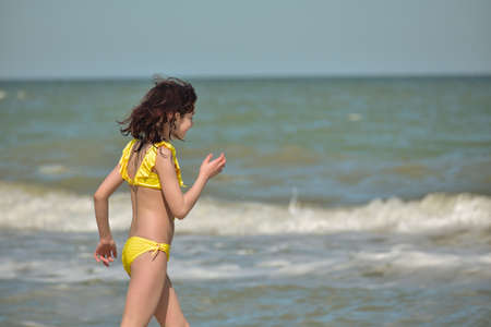 Girl at sea. The portrait of the young girl. Teenager summer vacation sand. Sunny day and the sea. Childhood travel vacation. Teenager in a yellow swimsuit on the beach. Teenager swims in the sea Banque d'images - 151517275