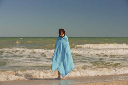 Girl at sea. The portrait of the young girl. Teenager summer vacation sand. Sunny day and the sea. Childhood travel vacation. Teenage in a blue towel on the beach. Portrait of a school-age girl