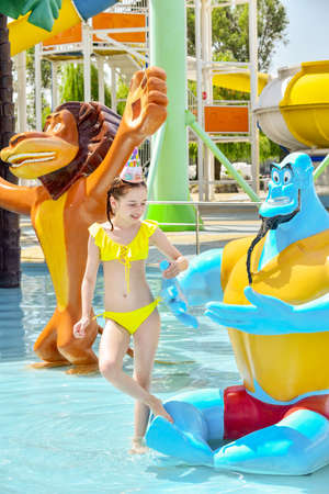 Young girl at a waterpark. Girl wearing a birthday cap at the water park. Little girl's birthday. Rest and celebration. A teenager on his birthday. Young slender girl in a yellow swimsuit. Childhood Stock Photo