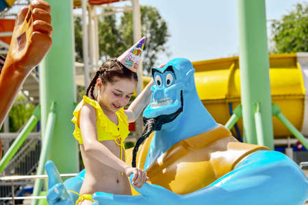 Young girl at a waterpark. Girl wearing a birthday cap at the water park. Little girl's birthday. Rest and celebration. A teenager on his birthday. Young slender girl in a yellow swimsuit. Childhood