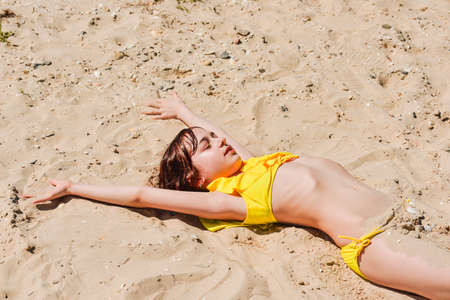 Young woman lies in summer on the beach. The girl lies on the sand on the beach. Teenager at sea. Vacation, summer, vacation, vacation. Child in a yellow swimsuit. Happinnes exists, Enjoying life
