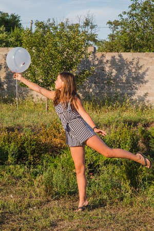 Outdoors portrait of beautiful young brunette girl. Brunette teen girl. Teenager girl and balloons. Girl, balloons, holiday, birthday. Happy moments in life. Girl 11-13 years old. Summer vacation,
