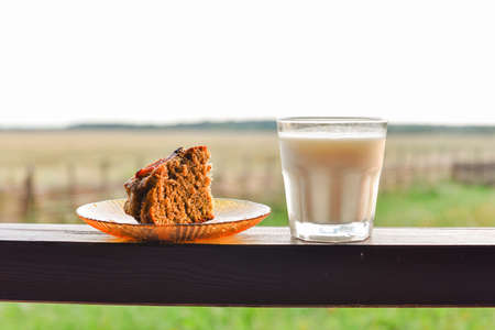 Bun with poppy seeds with a glass of milk. Milk in a glass and poppy seed cake on a field background. Pie with a cup of milk in the village on the background of the field. Beautiful nature and food. 版權商用圖片