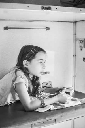 The girl rides a train in the summer on a trip. Vacation, train ride. A teenage girl rides a train. A school-age girl is lying on the top shelf in the train. Lifestyle