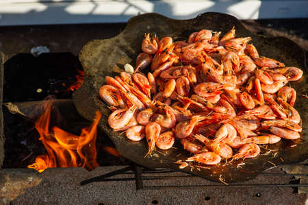 shrimp. Shrimps are cooked in a pan over a fire. Bonfire seafood. Food photography Foto de archivo