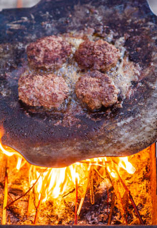 Burger Grilling on Fire. Homemade Hamburgers. Grill Meatballs. Making Hamburgers on a Grill Outdoor. Barbecue Grill Party. Meat Over Coals on Barbecue.Summer grilling. Foto de archivo