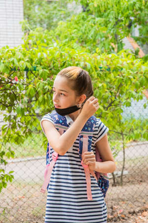 Schoolgirl girl in a black protective mask with a backpack. Schoolgirl in a school uniform. Fall. Back to school soon.