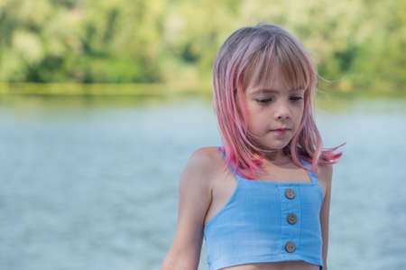 cute child girl portrait . Outdoor portrait of cute little girl in summer day. Portrait of a little girl with pink hair. Child 7-8 years old. Teenager