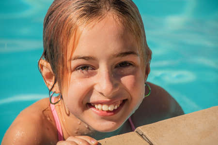 girl looking away while swimming in pool. excited girl looking away while swimming in pool. Joyful childhood. Relaxation concept. Relax by the pool, smile, teenager