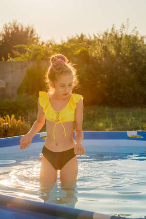 Joyful childhood. Relaxation concept. Relax by the pool, smile, teenager. A girl in a swimsuit in a frame pool is resting.