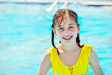 girl looking away while swimming in pool. excited girl looking away while swimming in pool. Joyful childhood. Relaxation concept. teenager. Girl laughing in a yellow bathing suit in the summer pool.
