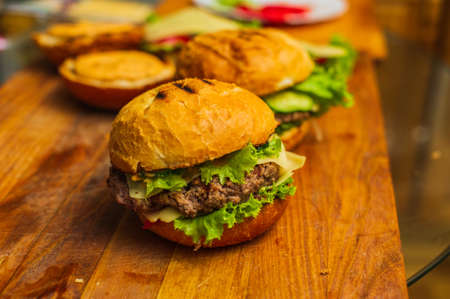 Two homemade grilled hamburgers on wooden board. Homemade burgers. Cooking homemade food