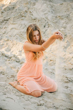 Girl on the background of sands. Portrait of a girl. Young girl with long blond natural hair in summer