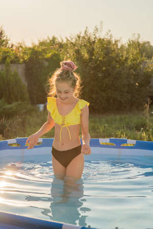 Joyful childhood. Relaxation concept. Relax by the pool, smile, teenager. A girl in a swimsuit in a frame pool is resting. Stock Photo