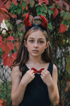 little girl in costumes for Halloween celebration. Halloween party, photo of Halloween characters. Autumn teenager portrait