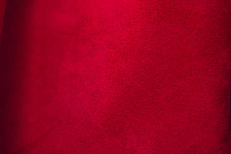 Red matte background of suede fabric, closeup. Velvet texture of seamless leather. Felt material macro. Red suede texture. Fabric, leather, material for designers. Stock Photo