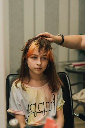 Hairdresser making a hair style to cute little girl. A teenage girl has her bangs lightened in a beauty salon. Orange bangs. The trend of bright hair.