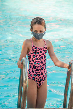 Girl child in a medical mask and swimsuit near the pool, the concept of rest and vacation during the epidemic and quarantine, protection and safety. Teenage girl in a mask near the pool