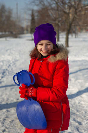 Little toddler girl in beautiful warm red outfit playing outdoors in the snow. Girl in a red jacket on the street in winter. A school age girl 9 or 10 years old in winter.