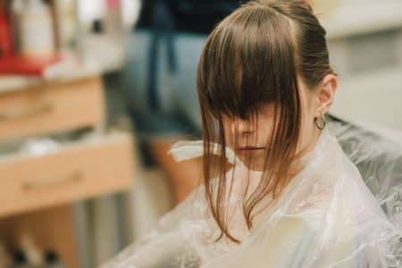 Hairdresser making a hair style to cute little girl. A teenage girl has her bangs lightened in a beauty salon. Orange bangs. The trend of bright hair. 版權商用圖片