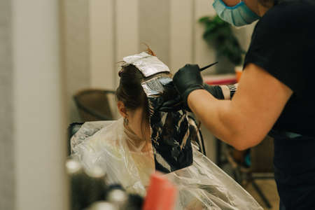 Hairdresser making a hair style to cute little girl. A teenage girl has her bangs lightened in a beauty salon. Orange bangs. The trend of bright hair. Stock fotó