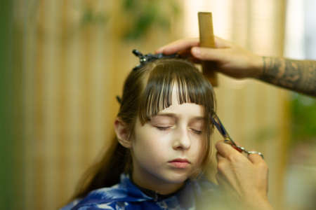 Little girl gets her bangs cut at beauty salon. Beauty concept