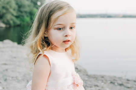 portrait of little girl outdoors in summer. Little girl in a dress in the summer by the river.Summer