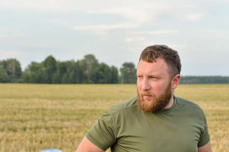 A man with a beard on the background of a haystack. Farmer in a field with hay