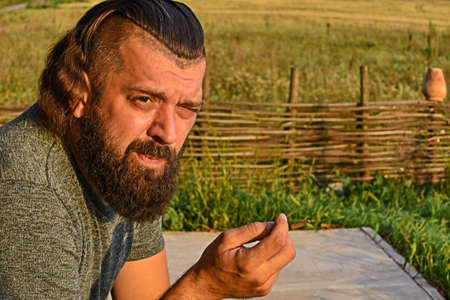 A man with a beard in a green T-shirt smokes a cigarette in nature. A man with long hair in a village.
