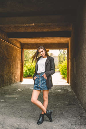 Girl in a denim skirt on the street in the spring. girl fashion style model. The girl in the arch.